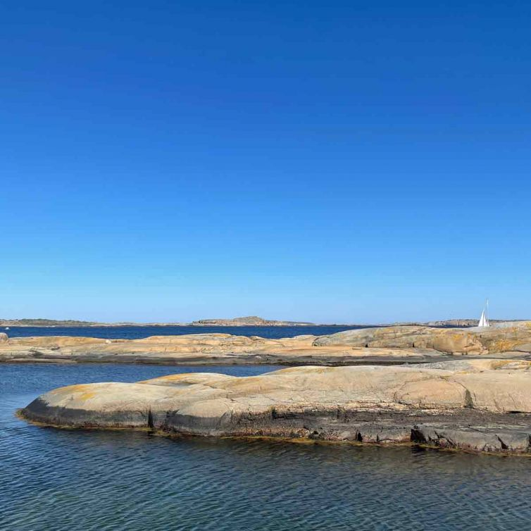 Svaberg og hav med et seil langt der ute.